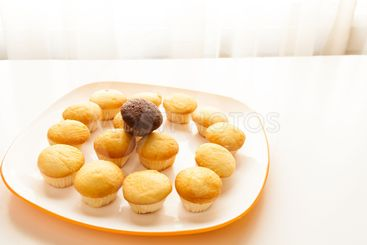 Tasty yellow muffins and chocolate muffin on top