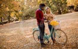 Multiracial couple with bicycle standing in the autumn...