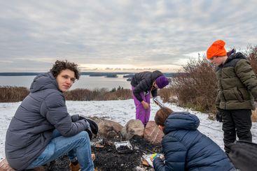 Familj grillar tillsammans utomhus i snön.