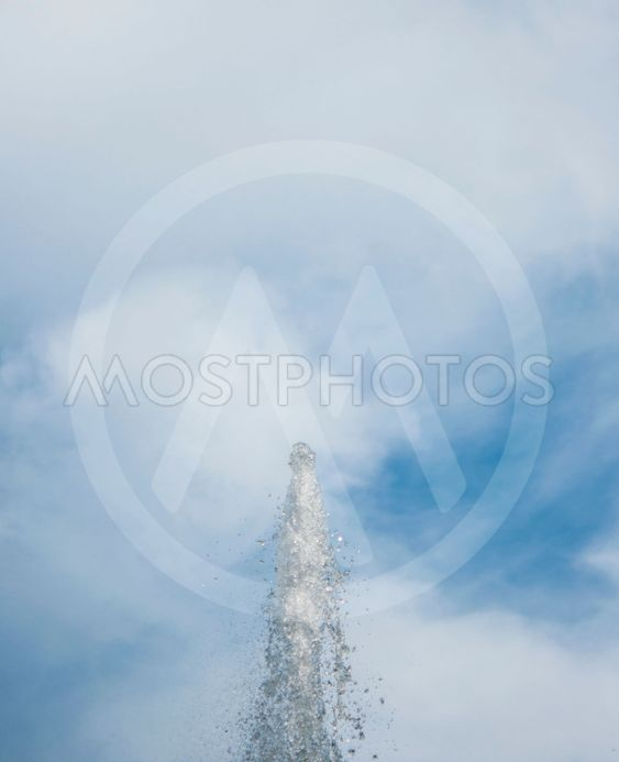splashes of water against the blue sky with clouds