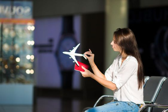 Pretty young female passenger with small model airplane...