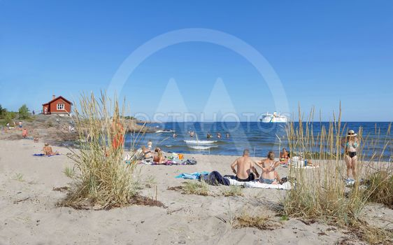 People relaxing on the beach watching a ferry, blue sky...