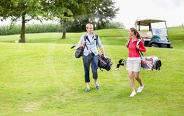 Golfing couple carrying their bags