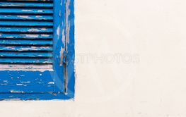 Blue wooden closed window on a white wall