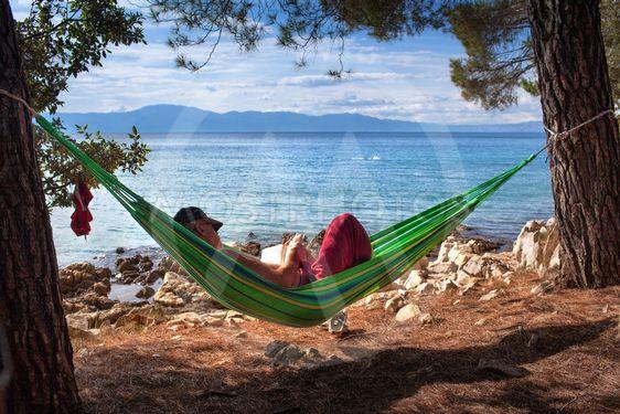 Man läser bok i hängmatta på strand