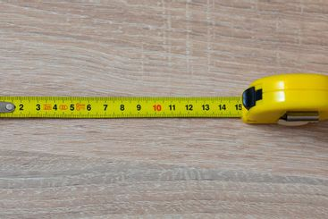 Tape measure on the table. Fifteen inches on a tape measure