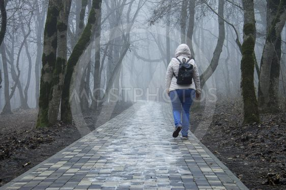 Lonely adult woman walking in autumn park in mysty morning