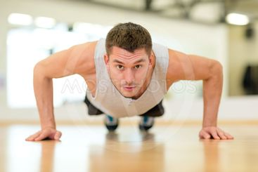 concentrated man doing push-ups in the gym