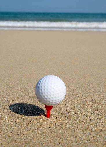 A golf ball on the beach, ready to be hit in to the ocean.