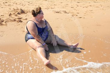 overweight woman sitting on beach