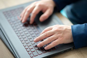Man's hands typing on a laptop keyboard