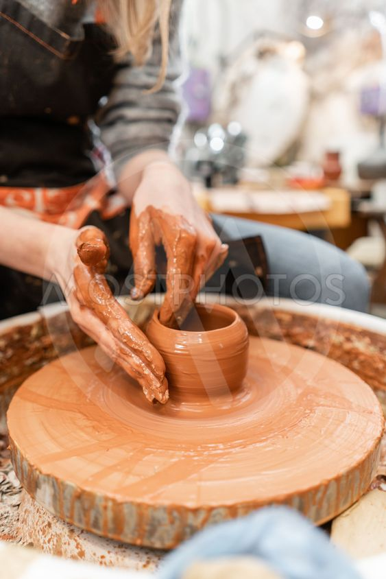 Craftsman hands making pottery bowl. Woman working on...
