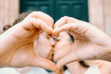 Young couple making a heart symbol with the hand and...