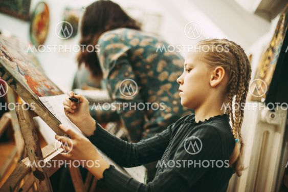 Beautiful teenage girl with pigtails at art school draws...