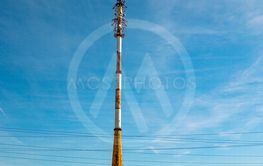 Mobile communications tower on a background of blue sky.