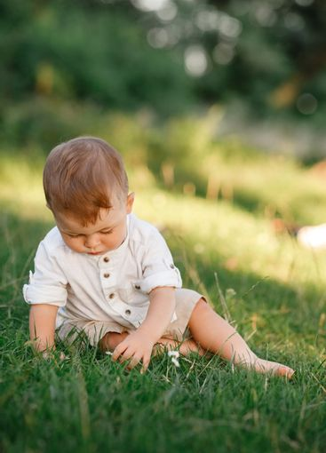 Happy adorable baby boy sitting on the grass in the park...