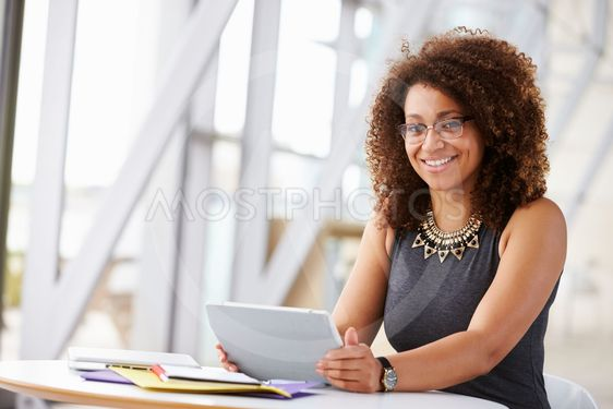African American woman with tablet, smiling to camera