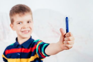 Cute child draws on the wall with colored crayons