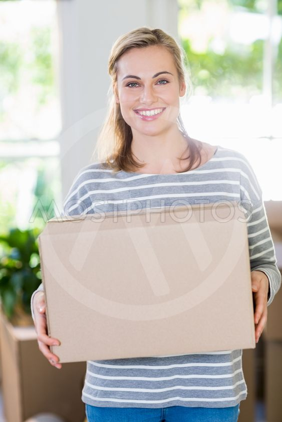 Portrait of young woman holding cardboard boxes