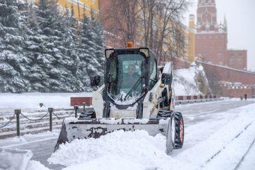A small loader excavator bobcat removes snow