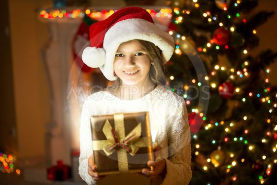 smiling girl posing with shining gift box against...