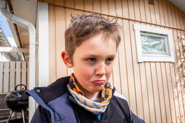 Porträtt av en sur, ledsen och arg pojke utomhus.