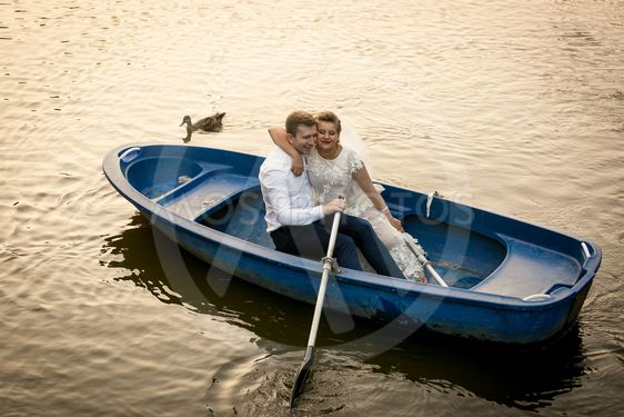 Smiling bride and groom embracing on the rowing boat