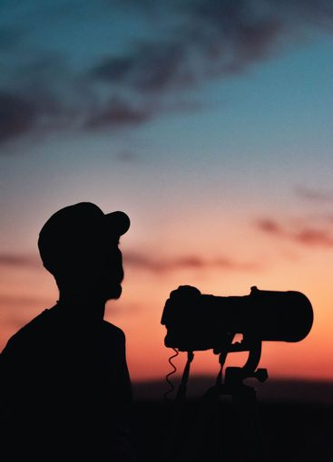 silhouette of wildlife photographer working at sunset...