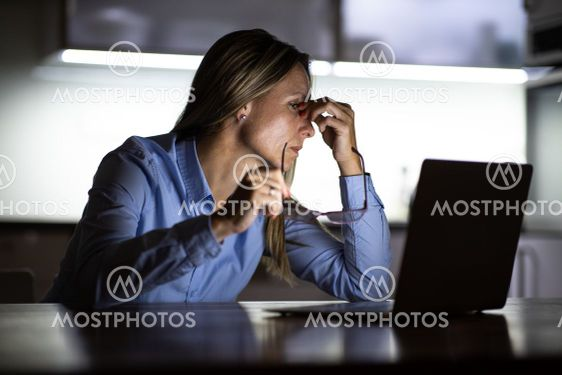 Pretty, middle-aged woman working late in the day on a...