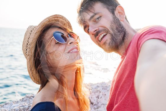Young couple taking a selfie by the sea