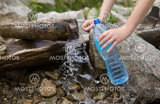 Taking spring water from a mountain spring.