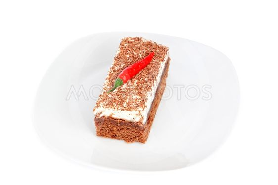 Piece of cake on a plate, and the fruit of paprika.