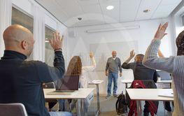 Elever med olika etnicitet räcker upp handen framför...