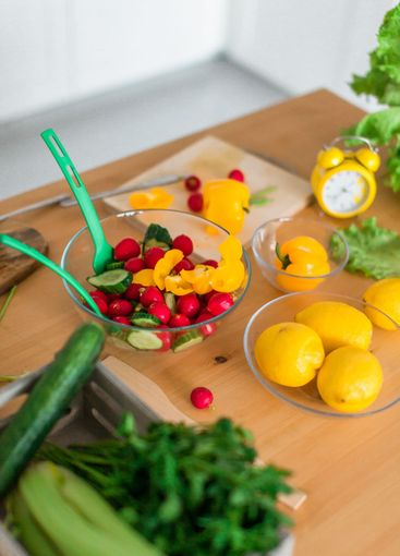 Colorful fresh vegetables and yellow timer alarm clock...
