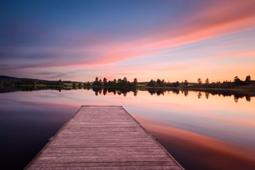 Dramatic sky over a idyllic lake with a jetty
