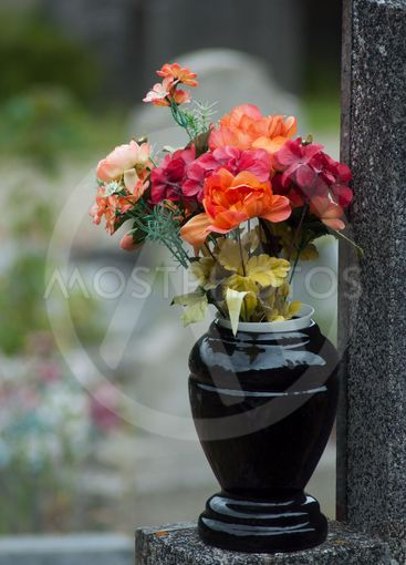 artificial flowers bouquet in pot on tomb in...