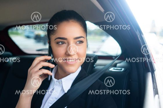 Businesswoman talking on phone in car.