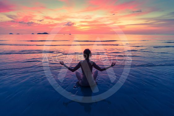 Young woman practicing yoga sitting on the sea beach...