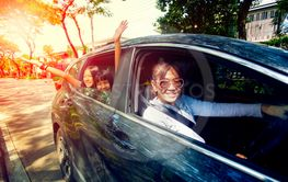 asian woman driving car with happiness teenager in...