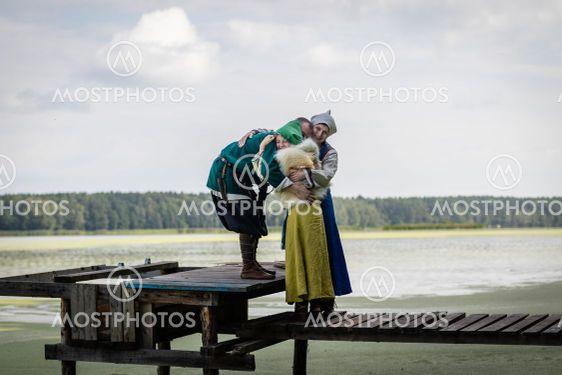 Viking family hugging on the footbridge by the lake
