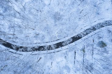 Aerial view of a road in a snowy forest in winter