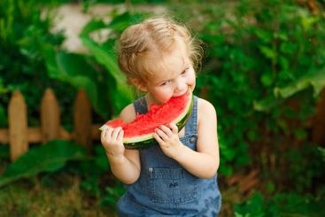 Little girl sit on watermelon and eating pieces