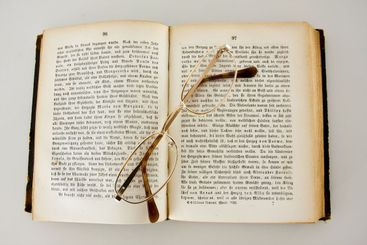 Reading glasses on an old book