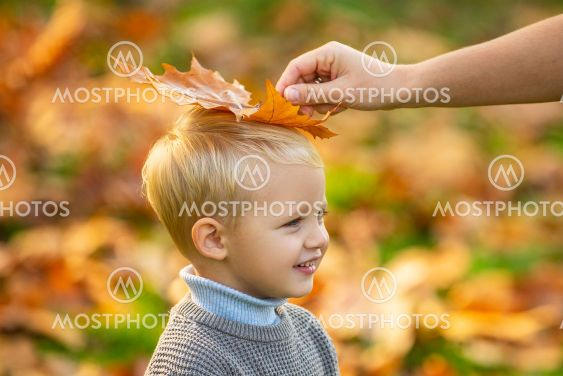Kid with autumn leaves in the beauty park, maple leaf....