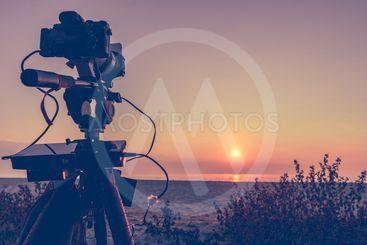 Camera taking picture film of sunrise over sea