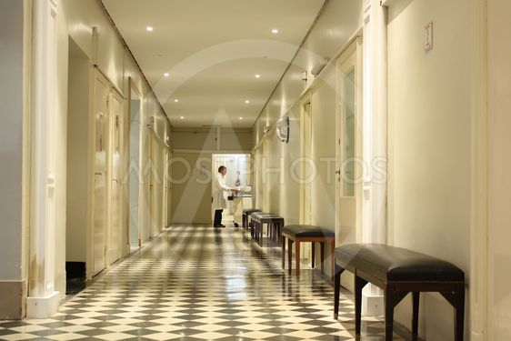 Doctor working at the end of a hospital hall