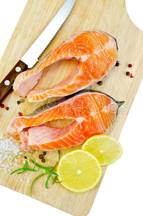 Trout with lemon and knife on plank