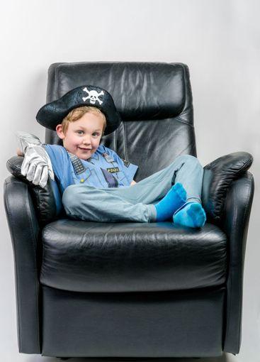 Glad liten pojke i fåtölj utklädd till polis och pirat.