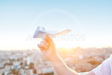 Young caucasian man's hand holding paper airplane in the...