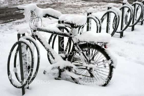 bicycle at the  station covered by the snow in the street